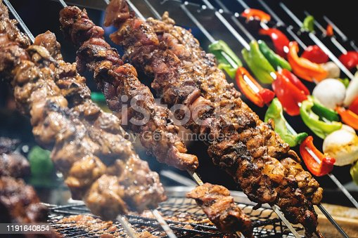 Close up kebabs on barbecue with some vegetables