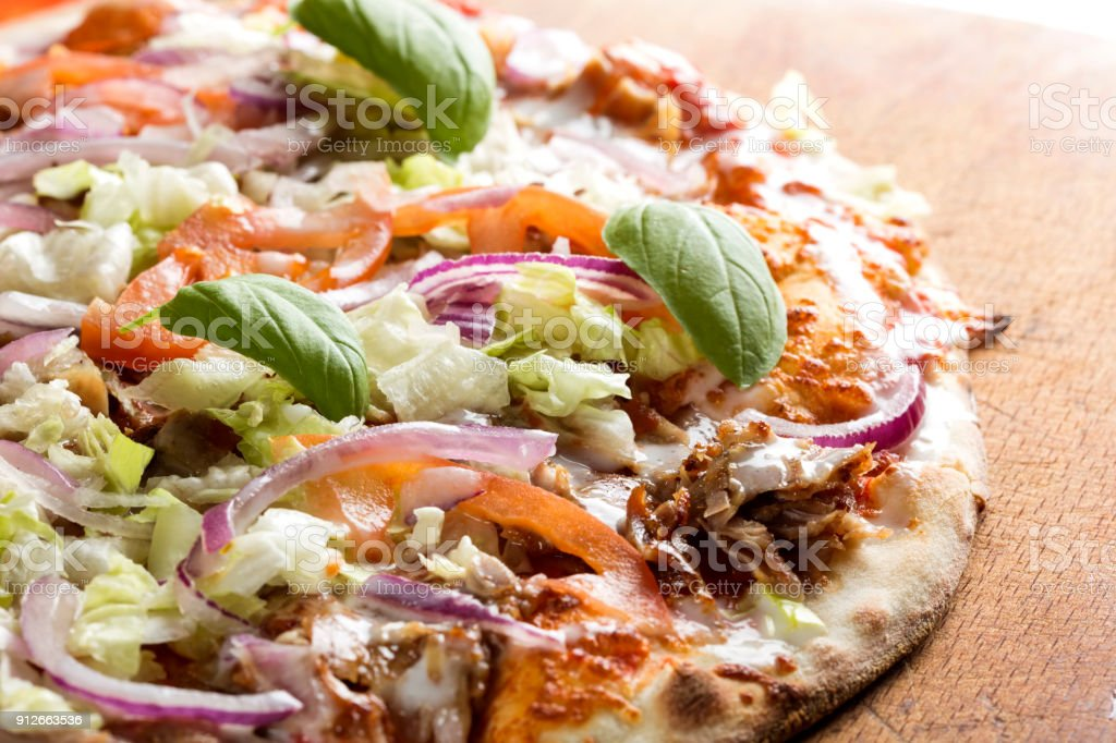 Kebap pizza made with minced meat, cabbage, tomato and garlic sauce stock photo