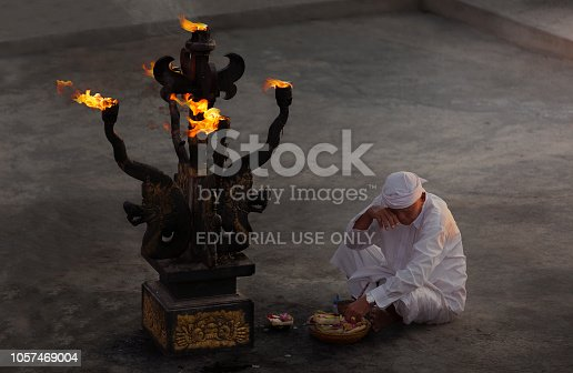 Uluwatu, Indonesia - September 21, 2015: A priest lights the altar and gives blessing to the site before the Kecak ceremony. Also known as the Ramayana Monkey Chant, it is a retelling of a great battle from the Ramayana of Hindu lore.