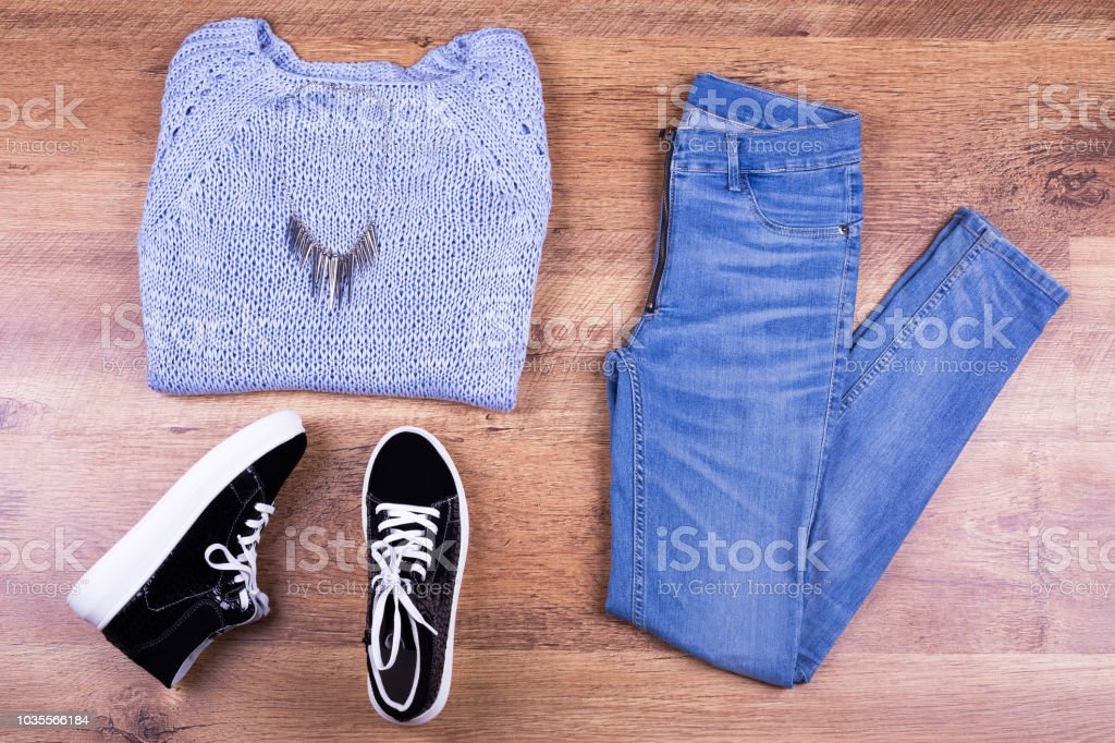 Keds, jeans, sweater and fashionable pendant stock photo