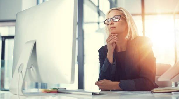 Keen business intuition Shot of a thoughtful businesswoman working at her desk in a modern office introspection stock pictures, royalty-free photos & images