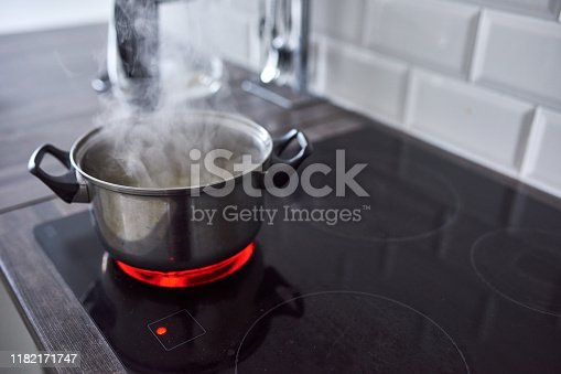 Shot of water boiling in an open pot on a hot stove at home