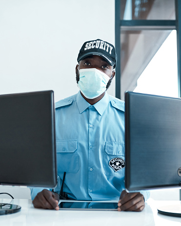 Portrait of a confident masked young security guard on duty at the front desk of an office