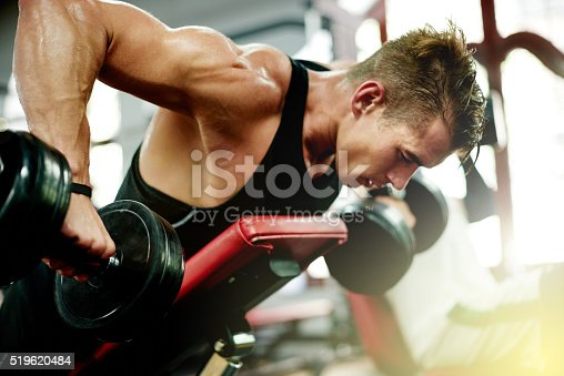 Shot of a young man working out at the gym
