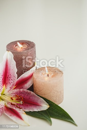Lily flower, candles on white background.