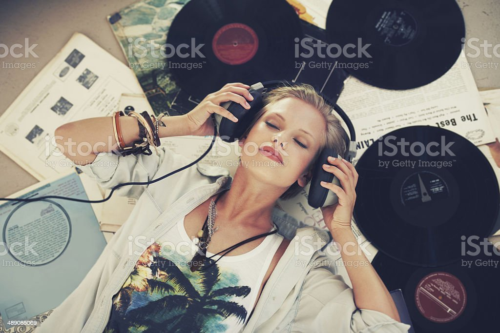 A young woman listening to music while lying on her back and...