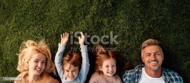 istock Keep calm and love your family. Happy family of four lying on green grass 1202686504