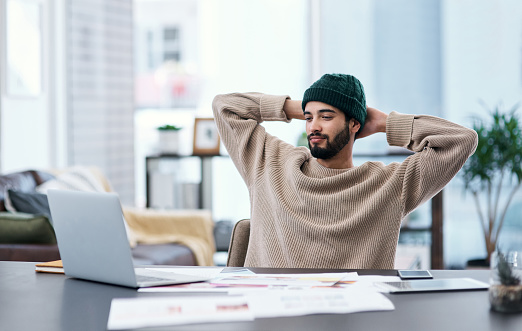 Shot of a young man taking a break while working from home