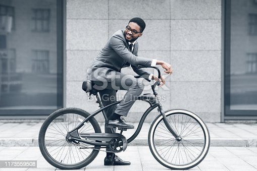istock Keep calm and ride on. Businessman cycling against office buiding 1173559508