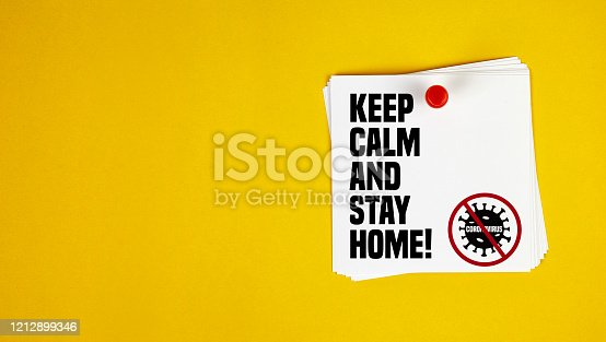 istock Keep Calm And Stay Home motivation letter written on post-it paper against Coronavirus 1212899346