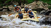 Shot of a group of determined young men on a rubber boat busy paddling on strong river rapids outside during the day