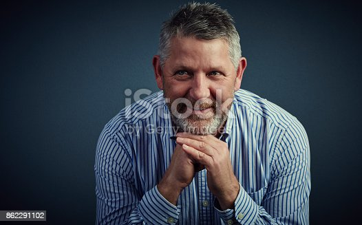 Studio shot of a confident and mature businessman looking thoughtful against a dark background