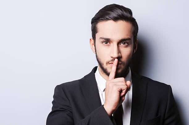 Keep my secret! Serious young man in formalwear holding finger on lips and looking at camera while standing against grey background finger on lips stock pictures, royalty-free photos & images