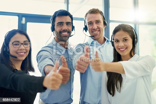 Portrait of a team of call centre agents showing thumbs up together in an office