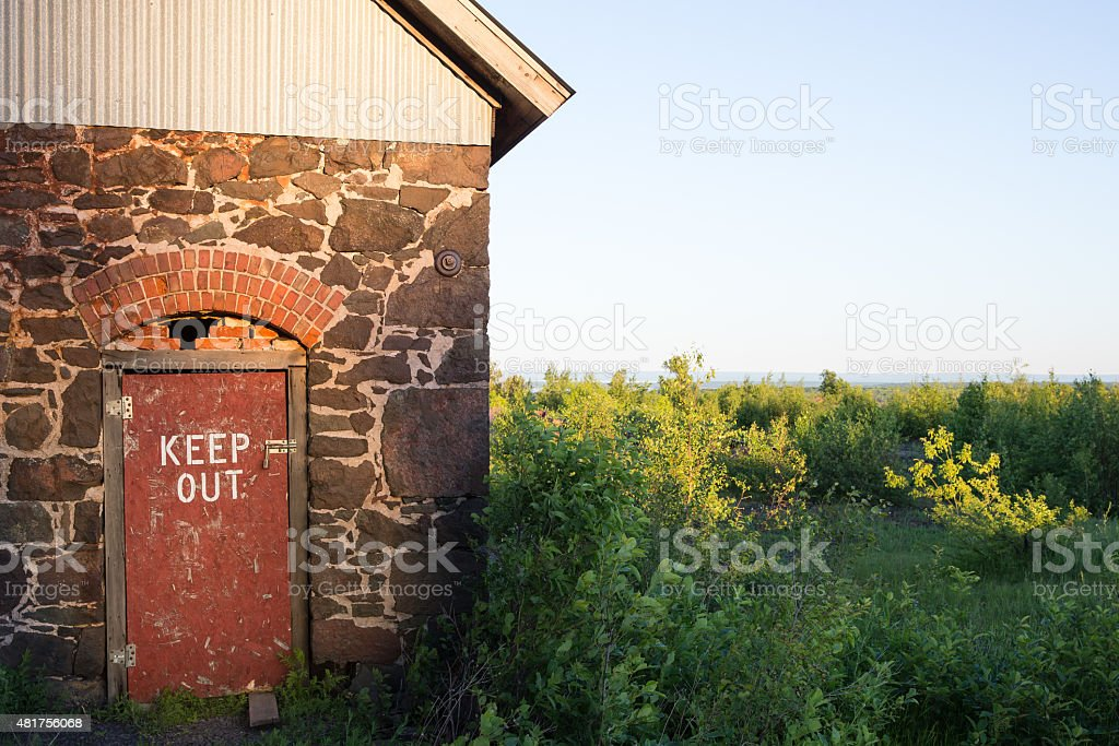 Keep Out Sign Stenciled on Rustic Red Door stock photo