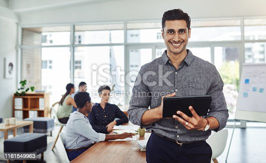 Portrait of a handsome young businessman using a digital tablet in an office with colleagues in the background