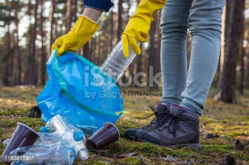 istock Keep the Earth clean! Volunteer is picking up plastic waste at nature. 1183812301