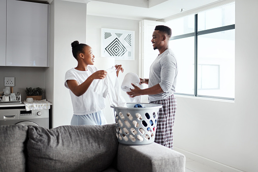 Shot of a happy young couple doing laundry together at home