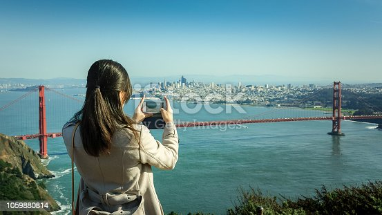 Girl taking a photo of San Francisco and Golden Gate bridge with an iphone