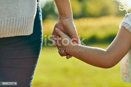 Cropped shot of a little girl holding an unrecognizable woman's hand in the park
