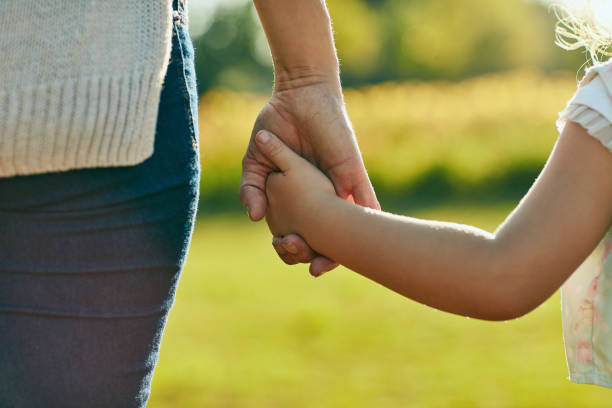 Keep them close, keep them safe Cropped shot of a little girl holding an unrecognizable woman's hand in the park holding hands stock pictures, royalty-free photos & images