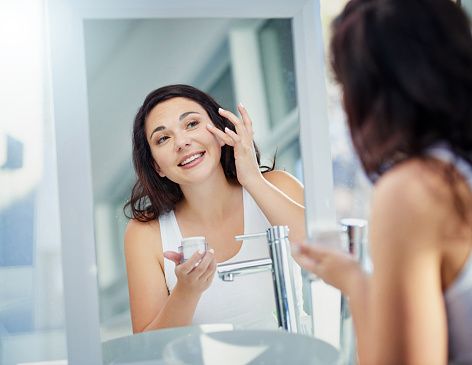Shot of an attractive young woman applying moisturiser in front of a bathroom mirror