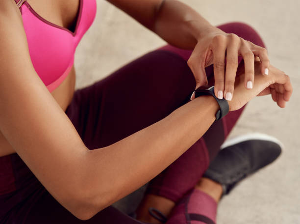 I keep track of every step I take Crossed shot of an unrecognizable woman using a smartwatch while out exercising fitness tracker stock pictures, royalty-free photos & images