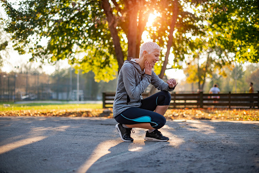 Senior Athletic Woman Checking Heart Rate After Running in the Park. Portrait of Mature Woman Check Her Pulse on Neck while Taking Break From Jogging