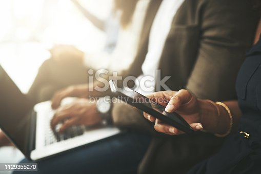 Cropped shot of a businesswoman using a smartphone while waiting in line