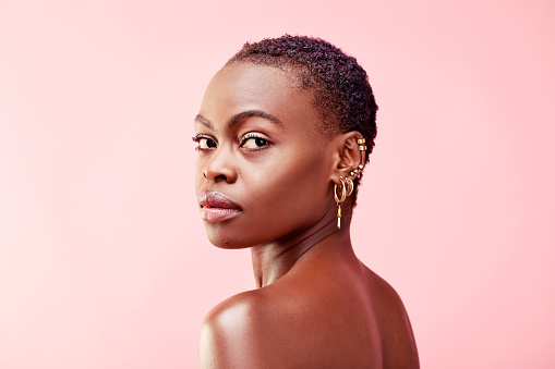 Studio portrait of a beautiful young woman posing against a pink background