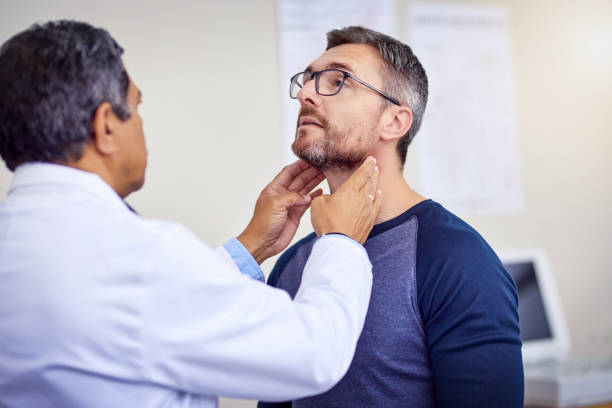 Keep your neck straight for me please Shot of a confident mature male doctor doing a checkup on a patient while standing inside of a hospital during the day axis deer stock pictures, royalty-free photos & images