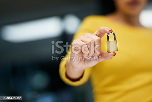 Closeup shot of an unrecognizable woman holding a padlock