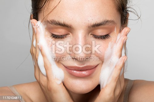 Close up studio shot of a beautiful woman with perfect skin, while she cleaning her face