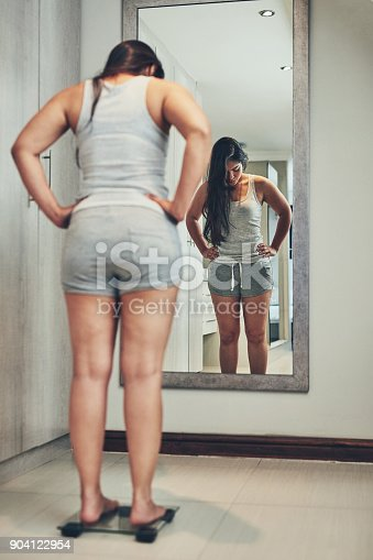 Shot of a young woman weighing herself on a scale at home