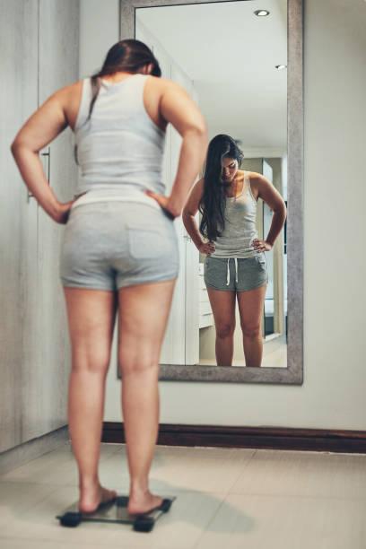 nauwlettend in de gaten houden op haar gewicht - lichaamsbewustzijn stockfoto's en -beelden