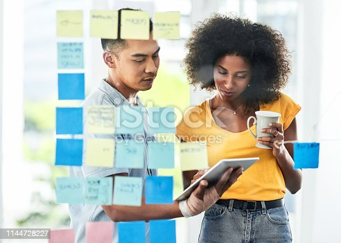 Shot of two businesspeople using a digital tablet while brainstorming with notes on a glass wall in an office