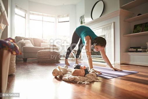 istock Keeping an eye on her baby while keeping in shape 628295056