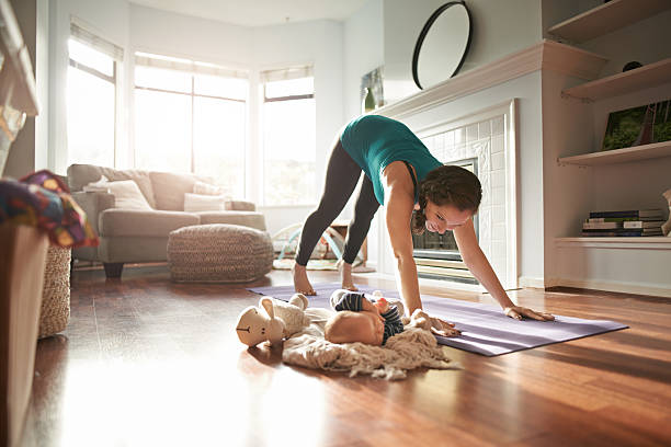 Keeping an eye on her baby while keeping in shape stock photo