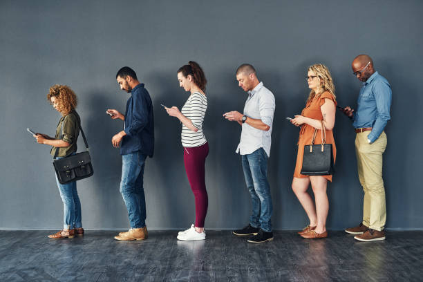 Keeping busy on their phones while they wait Studio shot of people waiting in line against a grey background people in a row stock pictures, royalty-free photos & images