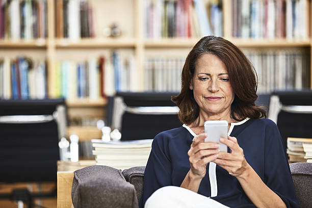 keeping connected throughout the business day - older woman phone stock photos and pictures