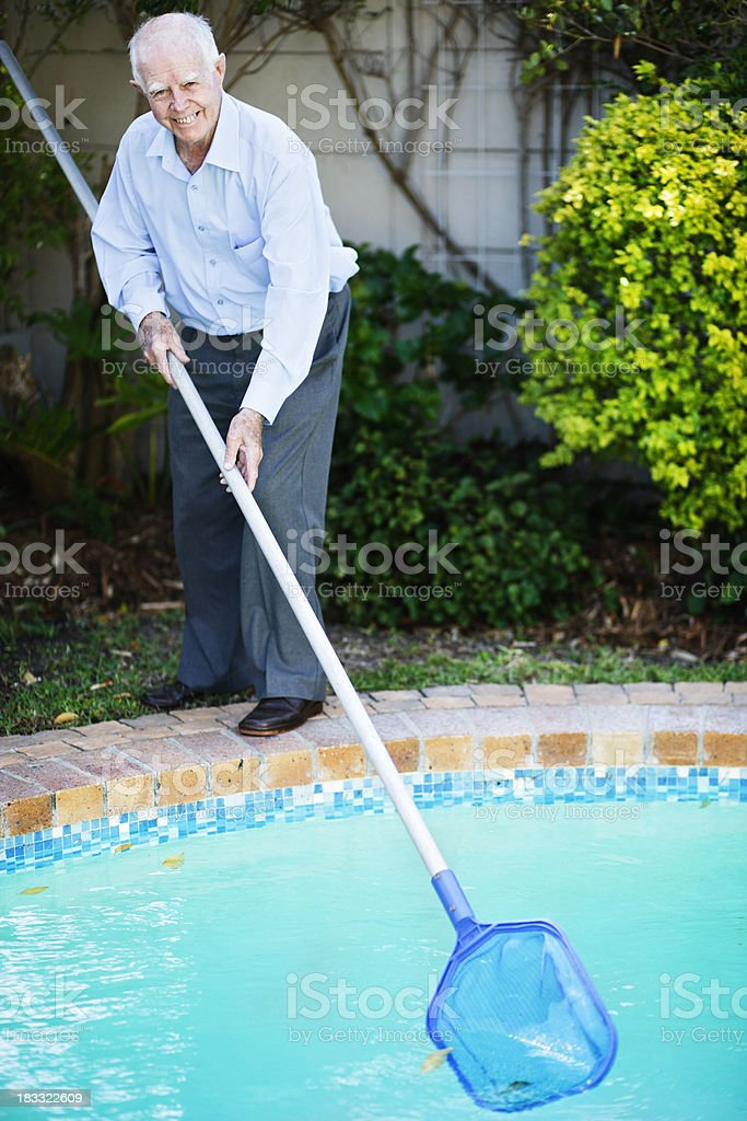 Keeping fit in old age; smiling man cleans swimming pool royalty-free stock photo