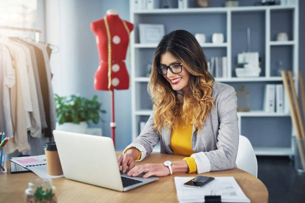 Keeping her boutique's website fresh and current Shot of a young woman using a laptop in her design studio fashion designer stock pictures, royalty-free photos & images