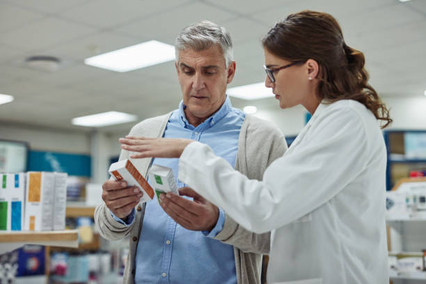 Keeping her customers healthy is her passion Shot of a young pharmacist helping a customer in a chemist pharmacist stock pictures, royalty-free photos & images