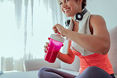 Close up Image of Young Fitness Woman With Headphones Drink Protein Shake While Sitting in Her Living Room After Workout. Young sporty woman athlete in sportswear sitting, drinking protein cocktail from shake