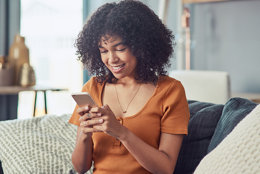 Shot of a young woman using a smartphone on the sofa at home