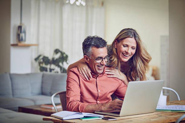 Keeping him company while he works Shot of a mature woman leaning on her husband while he works on his laptop mature couple stock pictures, royalty-free photos & images
