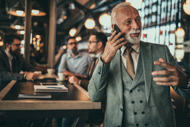 Keeping his client on the line Senior businessman using phone at the pub old man working in a pub stock pictures, royalty-free photos & images
