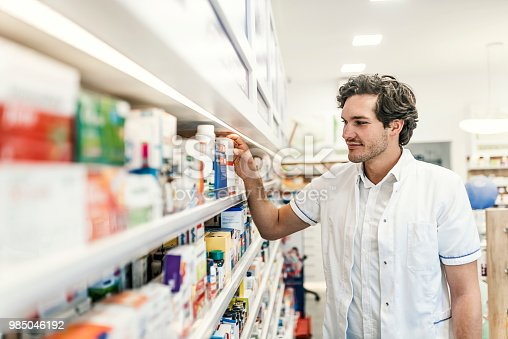 Photo of Caucasian young Apothecary in pharmacy standing at shelf with drugs, looking away. Small business owner: portrait of a male pharmacist at pharmacy.