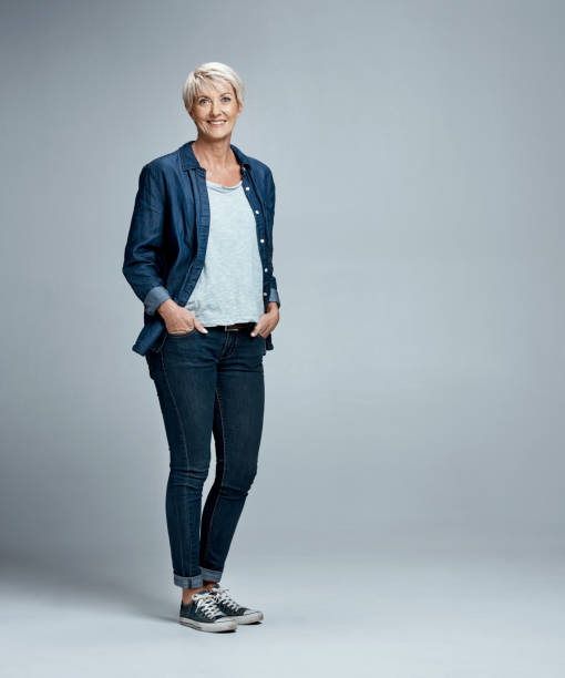 Keeping it cool and casual Studio portrait of a mature woman posing against a grey background hands in pockets stock pictures, royalty-free photos & images