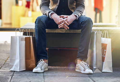Shot of a man sitting on a bench with his shopping bags on the floor